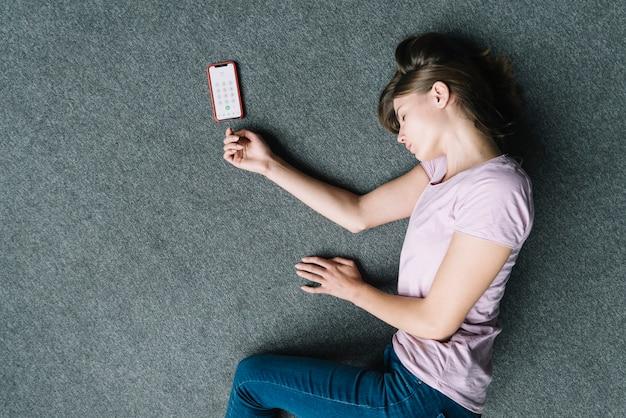 Punto di vista ambientale della donna incosciente che si trova vicino al telefono cellulare su tappeto Foto Gratuite