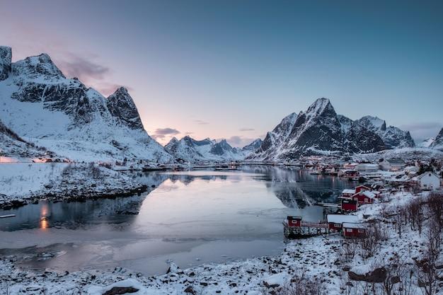 Punto di vista del paesino di pescatori con il porto nella valle della neve e sul mare del ghiaccio alla mattina Foto Premium