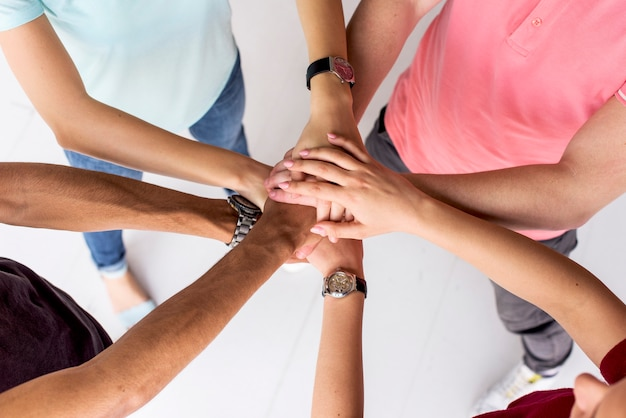 Punto di vista dell'angolo alto degli amici che impilano insieme le loro mani Foto Gratuite