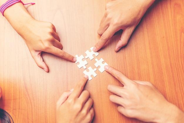 Punto di vista dell'angolo alto della mano delle persone di affari che risolve puzzle sullo scrittorio di legno Foto Premium