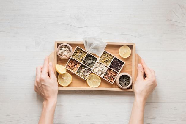 Punto di vista dell'angolo alto della mano di una persona che tiene vassoio di legno con le erbe e le foglie di tè asciutte Foto Gratuite
