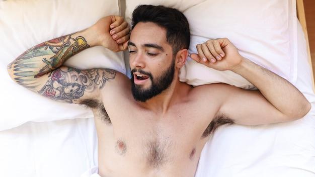 Punto di vista dell'angolo alto di un giovane senza camicia che dorme sul letto Foto Gratuite