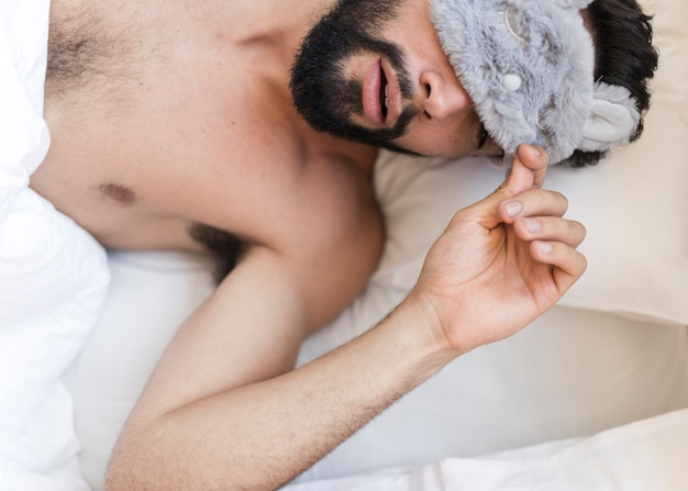 Punto di vista dell'angolo alto di un uomo senza camicia che dorme sul letto con una maschera per gli occhi Foto Gratuite