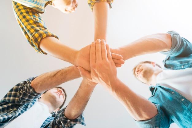 Punto di vista di angolo basso degli amici maschii che impilano le mani contro il fondo bianco Foto Gratuite