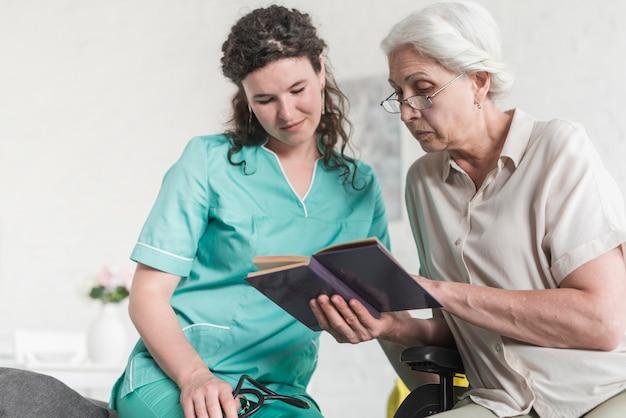 Punto di vista di angolo basso dell'infermiere femminile che esamina il libro di lettura senior della donna Foto Gratuite