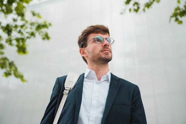 Punto di vista di angolo basso di giovane uomo d'affari che si leva in piedi contro la parete che osserva via Foto Gratuite