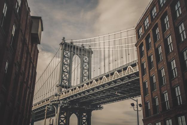 Punto di vista di dumbo che può vedere il ponte di manhattan con la vecchia costruzione di mattone a new york city, usa Foto Premium