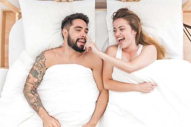 Punto di vista elevato della donna felice che tocca il naso del suo ragazzo sul letto Foto Gratuite