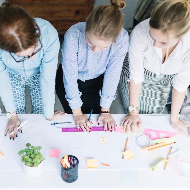 Punto di vista elevato delle donne di affari che progettano il grafico di affari su carta sopra lo scrittorio Foto Gratuite