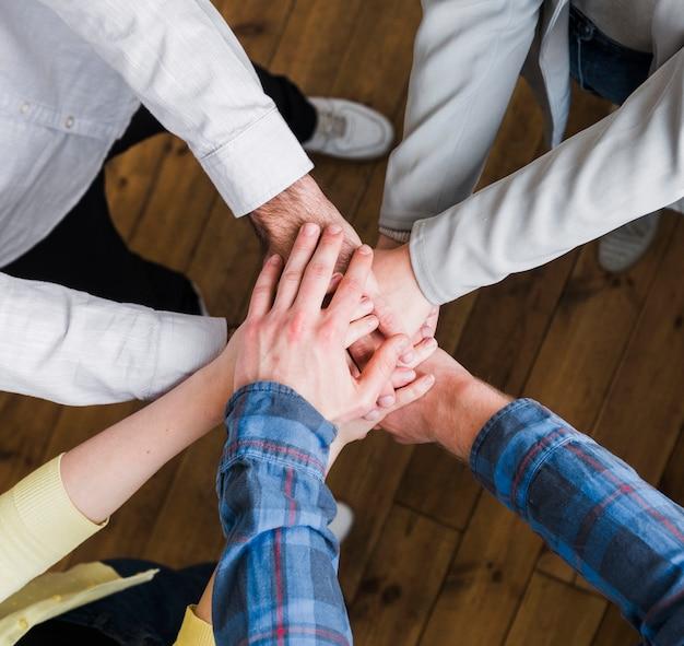 Punto di vista elevato delle persone di affari che impilano le mani sopra a vicenda Foto Gratuite