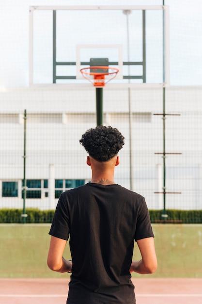 Punto di vista posteriore del maschio anonimo atletico al campo da pallacanestro Foto Gratuite