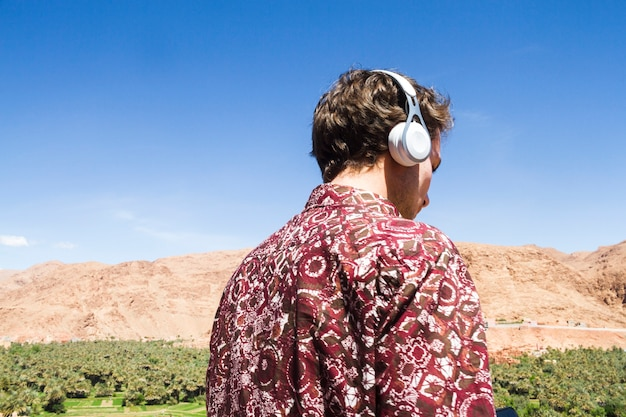 Punto di vista posteriore dell'uomo che ascolta la musica in oasi Foto Gratuite