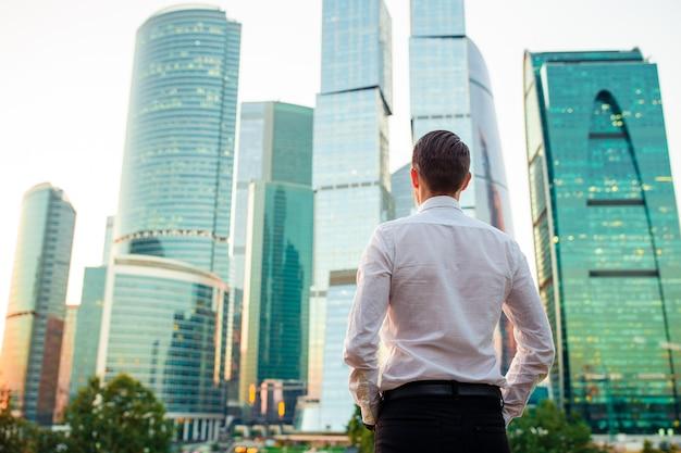 Punto di vista posteriore dell'uomo d'affari che guarda sullo spazio della copia mentre stando contro il grattacielo di vetro Foto Premium