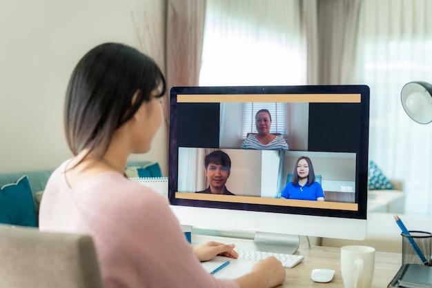 Punto di vista posteriore della donna asiatica di affari che parla con suoi colleghi del piano nella videoconferenza. Foto Premium