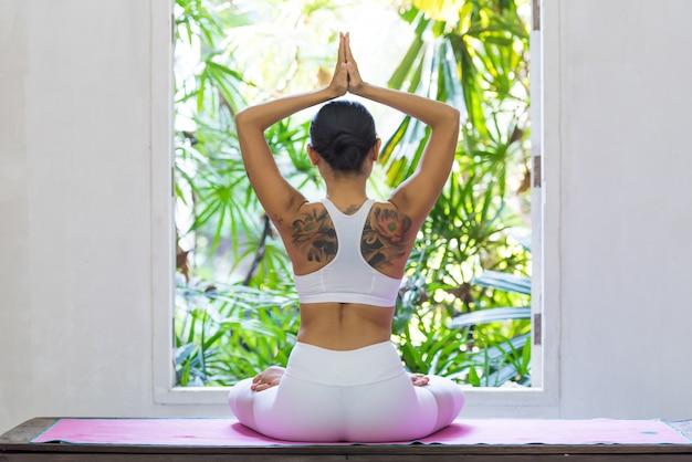 Punto di vista posteriore della donna che fa posa di yoga alla finestra Foto Premium