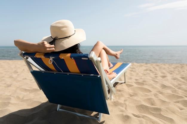 Punto di vista posteriore della donna che si siede sulla sedia di spiaggia che esamina il mare Foto Gratuite