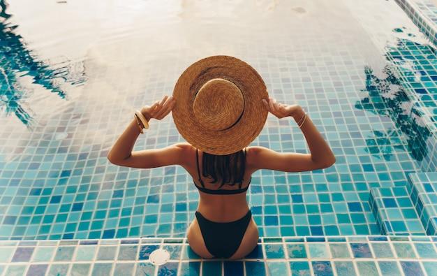 Punto di vista posteriore della donna graziosa in costume da bagno e cappello che si siedono vicino allo stagno Foto Gratuite