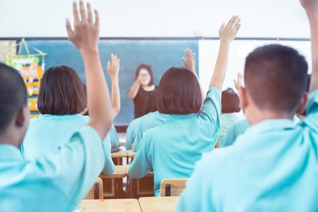 Punto di vista posteriore dello studente asiatico che si siede nella classe e che solleva mano su per fare domanda durante la conferenza. Foto Premium