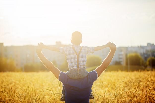 Punto di vista posteriore di un padre con suo figlio sulle spalle che stanno in un campo e città sul tramonto di estate Foto Premium