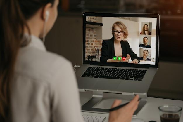 Punto di vista posteriore di una donna a casa che parla con il suo capo e altri colleghi in una videochiamata su un computer portatile. la donna di affari parla con i colleghe su una conferenza della webcam. squadra di affari che ha una riunione online. Foto Premium