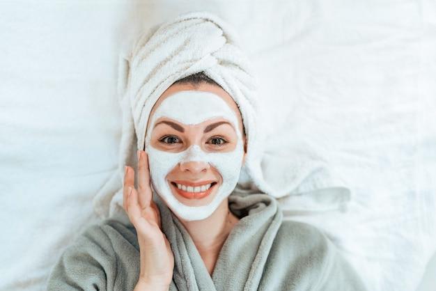 Punto di vista superiore della giovane donna sorridente con la maschera facciale che si riposa e che esamina macchina fotografica. Foto Premium
