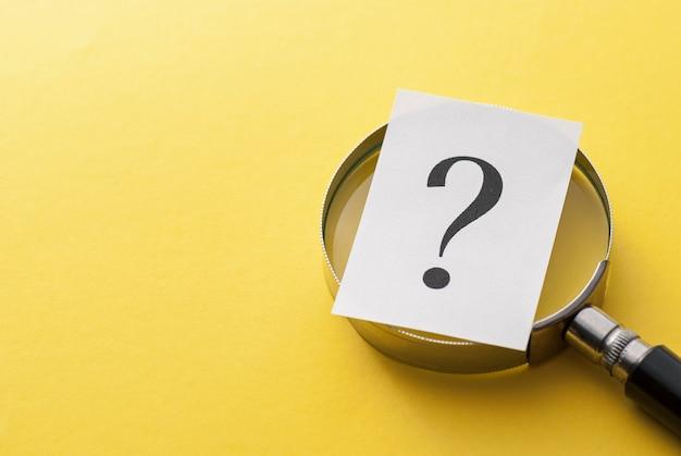 Punto interrogativo stampato che copre una lente d'ingrandimento Foto Premium