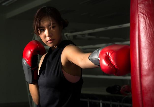 Punzone femminile del pugile all'obiettivo in palestra, sport di pugilato Foto Premium