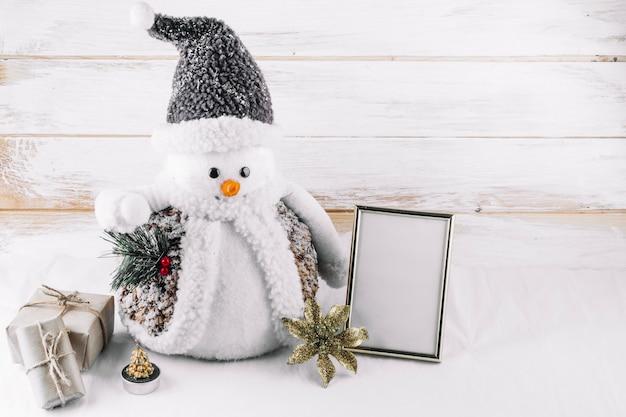 Pupazzo di neve con cornice vuota sul tavolo Foto Gratuite