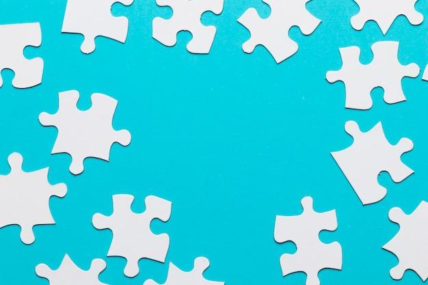 Puzzle bianchi sparsi su sfondo blu Foto Gratuite