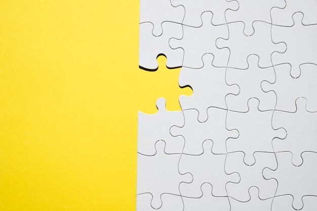 Puzzle bianco con un pezzo mancante sul fondale giallo Foto Gratuite