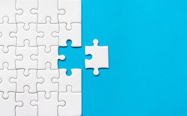 Puzzle bianco su sfondo blu. collaborazione o lavoro di squadra successo aziendale. Foto Premium