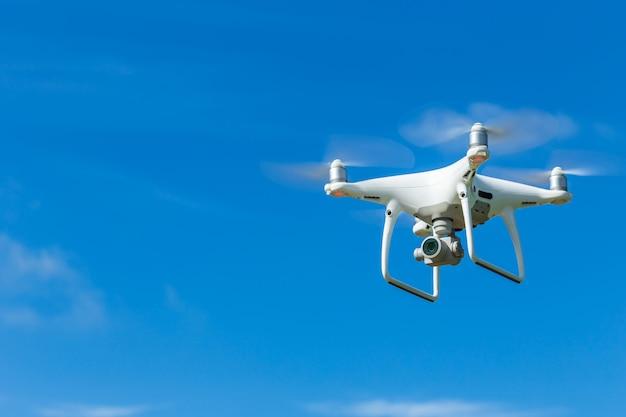 Quadcopter del fuco di volo con la macchina fotografica digitale su cielo blu Foto Premium