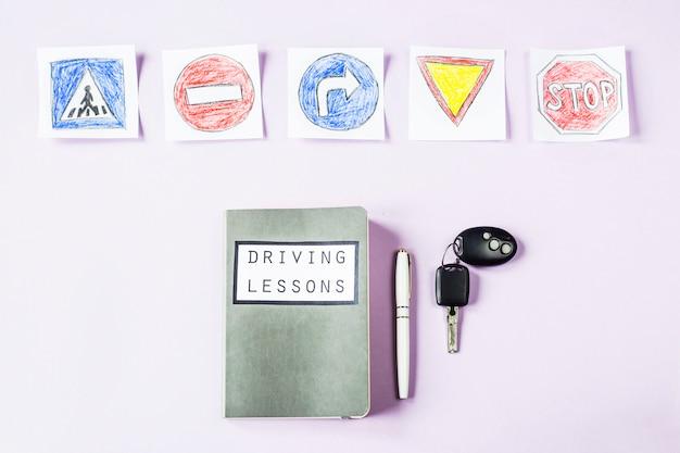 Quaderno di allenamento per lezioni di guida e regole del traffico di guida accanto ai disegni dei cartelli stradali per ottenere una patente di guida Foto Premium