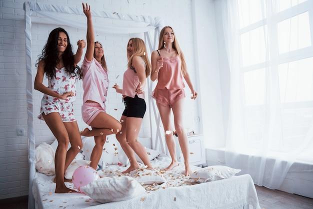 Qualche danza folle. confetti in the air. le ragazze si divertono sul letto bianco nella bella stanza Foto Gratuite