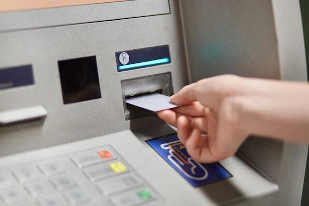 Qualcuno toglie denaro dal terminal bancario esterno, inserisce la carta di credito in plastica nella macchina bancomat, andando a prelevare denaro e ottenere uno stipendio Foto Premium