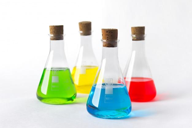 Quattro boccette del laboratorio con le spine del sughero e liquidi variopinti isolati su bianco. Foto Premium