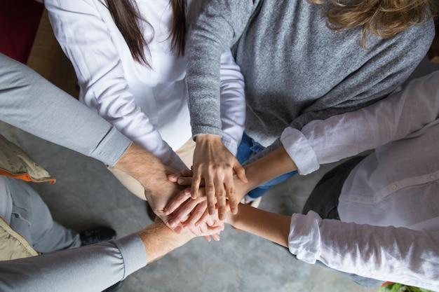 Quattro colleghi che uniscono le mani Foto Gratuite