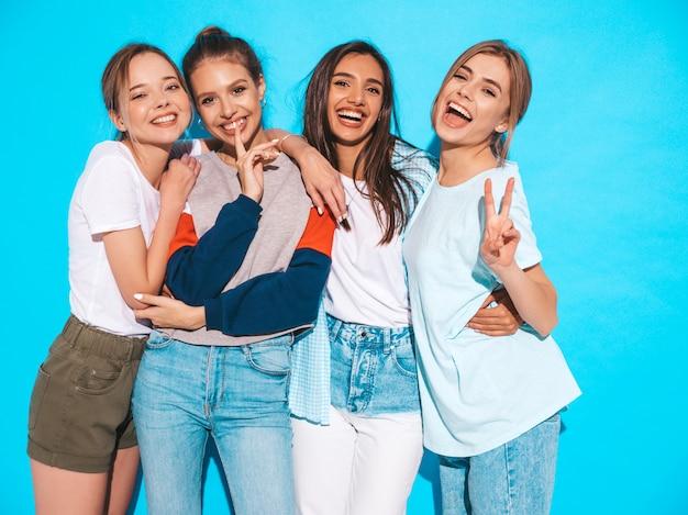 Quattro giovani belle ragazze sorridenti hipster in abiti estivi alla moda. donne spensierate sexy che posano vicino alla parete blu in studio. modelli positivi che si divertono e si abbracciano Foto Gratuite