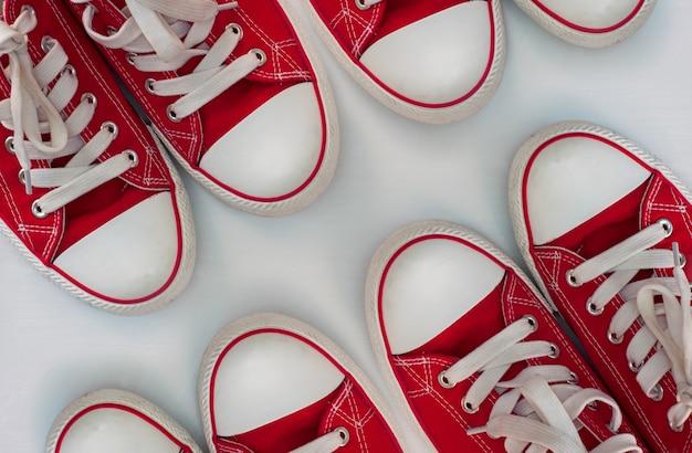 Quattro paia di scarpe da ginnastica rosse su una superficie di legno bianca Foto Premium