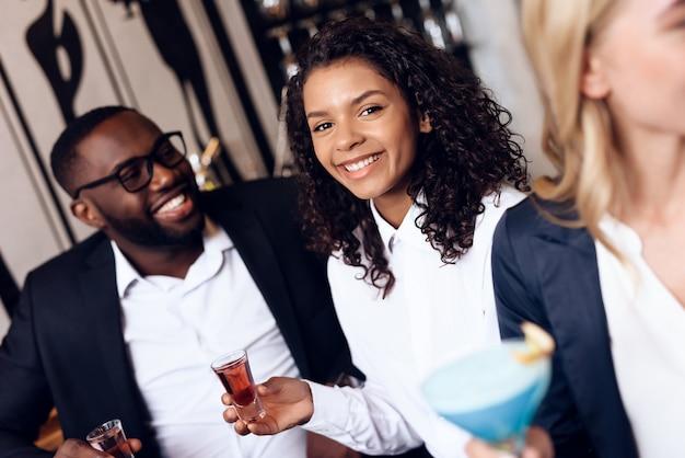 Quattro ragazzi e ragazze bevono cocktail in un bar. Foto Premium