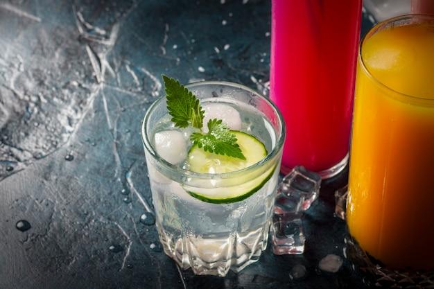 Quattro tipi di bevande rinfrescanti con ghiaccio su una superficie blu scuro e cubetti di ghiaccio. Foto Premium