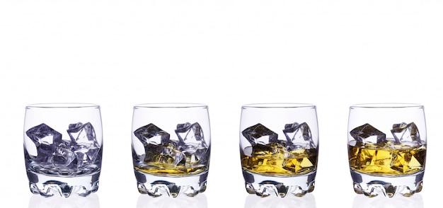 Quattro vetri di whiskey con i cubetti di ghiaccio su un isolato bianco del fondo. Foto Premium