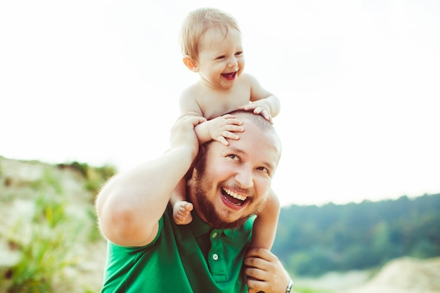 """""""Padre a pelo corto che porta il bambino sulle spalle"""" Foto Gratuite"""