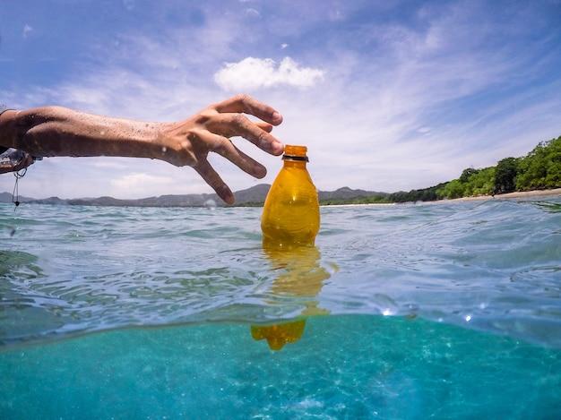 Raccogliendo una bottiglia di plastica dall'ocwan, ricicla Foto Premium