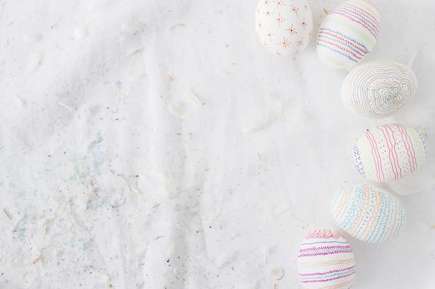 Raccolta di uova di pasqua con modelli vicino a spolette sul tessile Foto Gratuite