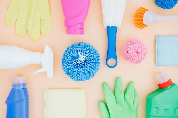 Raccolta di vista superiore di prodotti per la pulizia colorati su sfondo di pesca Foto Gratuite