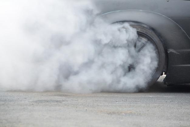 Racing car burning rubber tire on spinning wheel with white smoke Foto Premium