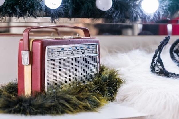 Radioricevitore vintage su pelliccia bianca davanti al tavolo da trucco. Foto Premium