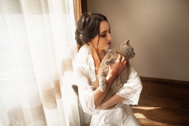 Raduno mattutino della sposa nella bellissima sala luminosa con il suo gatto Foto Premium