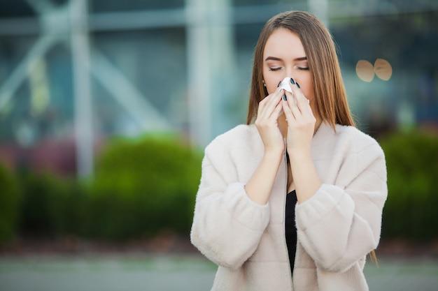 Raffreddore e influenza. giovane ragazza attraente, preso un raffreddore per strada, si asciuga il naso con un tovagliolo Foto Premium